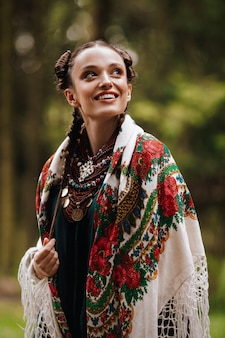 Ragazza felice nei sorrisi ucraini tradizionali dei vestiti