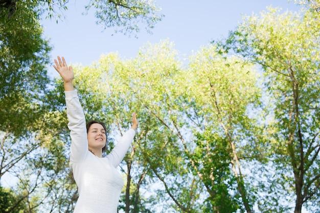 Ragazza felice nel bianco nel parco verde. camminando sulla natura
