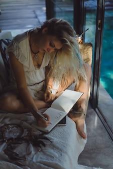 Ragazza felice passa il tempo a casa in un interno accogliente, scrive e disegna in un quaderno.