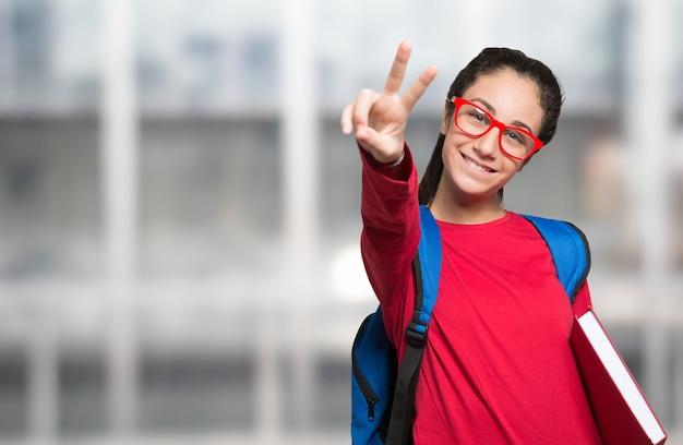 Ragazza felice sorridente dello studente con gli occhiali che tengono un libro, copia-spazio sulla sua parte di sinistra