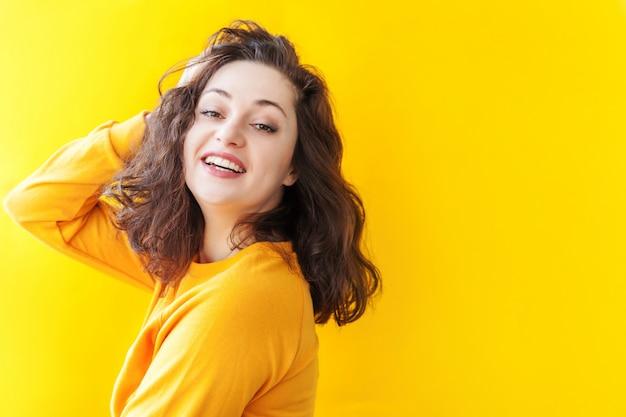 Ragazza felice sorridente giovane donna castana di risata positiva felice del ritratto di bellezza su fondo giallo isolato. donna europea. emozioni umane positive espressione facciale linguaggio del corpo