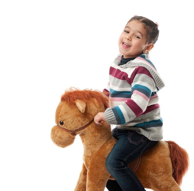 Ragazza felice sul cavallo a dondolo