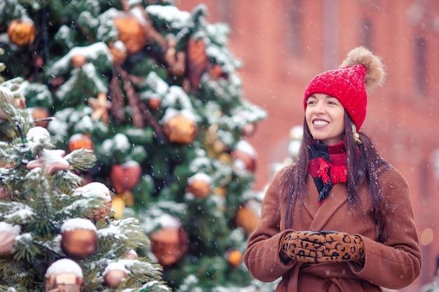Ragazza felice vicino al ramo dell'abete in neve per il nuovo anno.
