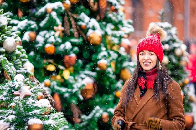 Ragazza felice vicino al ramo di albero dell'abete in neve per il nuovo anno.