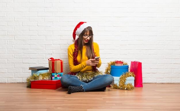 Ragazza festeggia le vacanze di natale inviando un messaggio o un'email con il cellulare