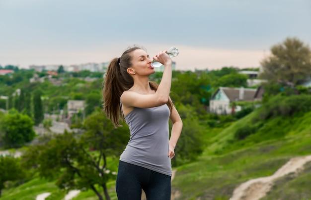 Ragazza fitness assetato tenendo la bottiglia d'acqua