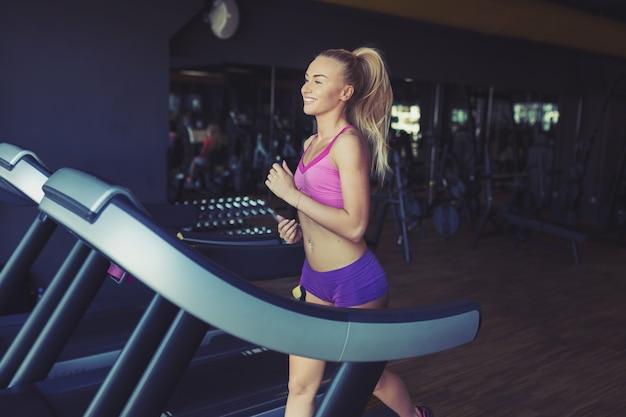 Ragazza fitness in esecuzione sul tapis roulant