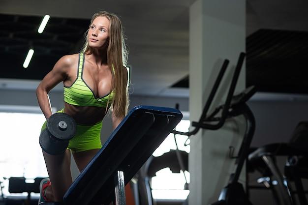 Ragazza fitness si allena in palestra, facendo esercizi con un bilanciere