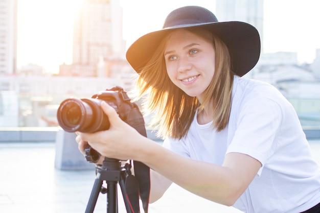 Ragazza fotografa con una macchina fotografica e un treppiede su uno sfondo della città, fotografa al tramonto, una donna gira un video