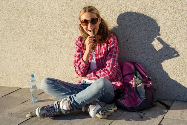 Ragazza fresca sorridente dei giovani, calzata sui pattini di rullo che mangia la barra di cioccolato