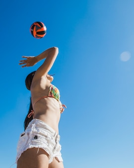 Ragazza giocare a pallavolo vista dal basso