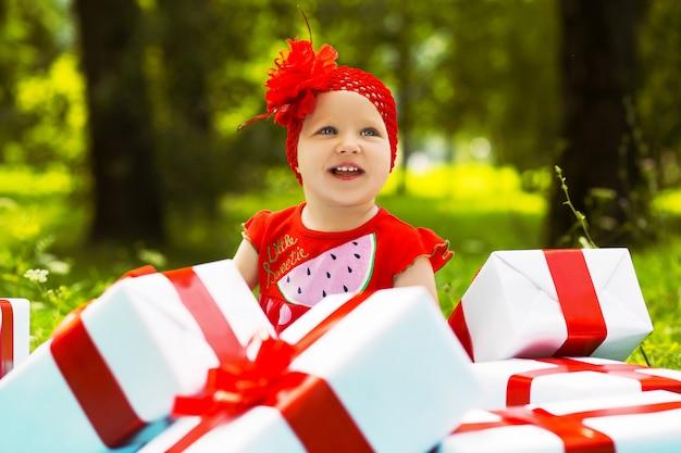 Ragazza gioiosa bambino con scatole regalo colorate