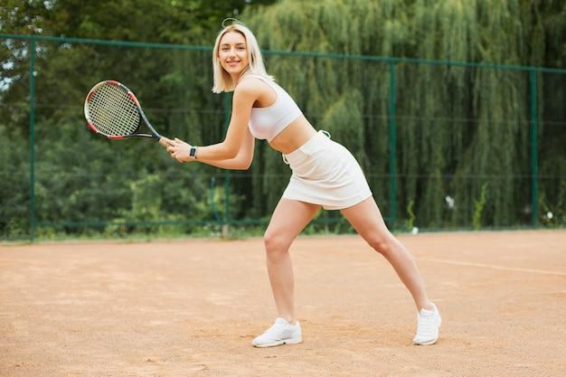 Ragazza giovane adatta che gioca a tennis
