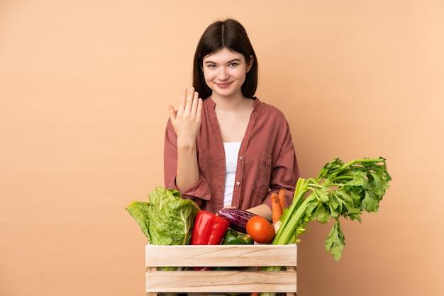 Ragazza giovane agricoltore con verdure appena raccolte in una scatola che invita a venire con la mano