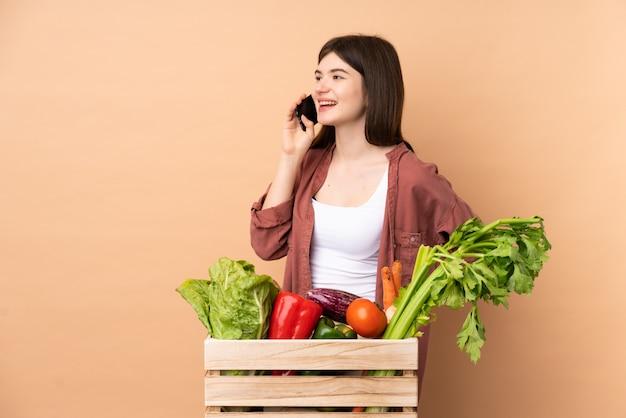 Ragazza giovane agricoltore con verdure appena raccolte in una scatola mantenendo una conversazione con il telefono cellulare