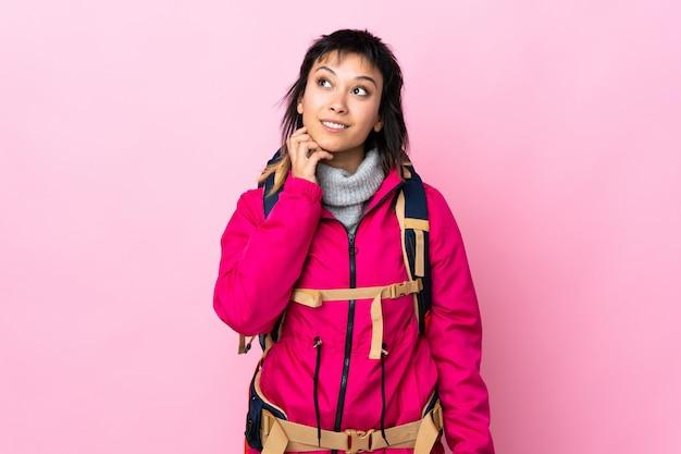 Ragazza giovane alpinista con un grande zaino sopra fondo rosa isolato che pensa un'idea
