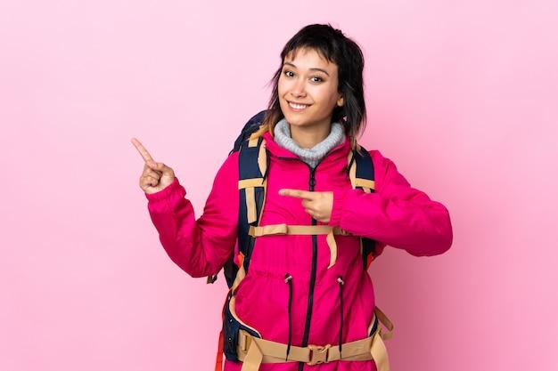 Ragazza giovane alpinista con un grande zaino sopra il dito puntato rosa isolato sul lato
