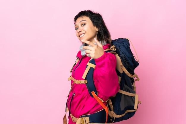 Ragazza giovane alpinista con un grande zaino su invito isolato rosa a venire