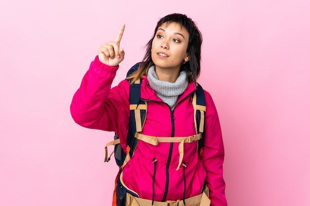 Ragazza giovane alpinista con un grande zaino su sfondo rosa isolato toccando sullo schermo trasparente