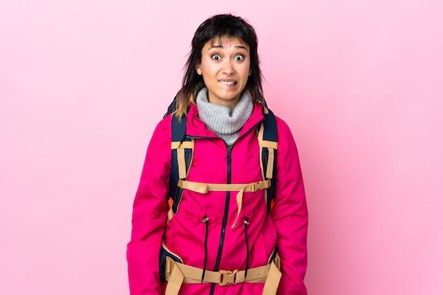 Ragazza giovane alpinista con un grande zaino sul muro rosa con dubbi e con espressione faccia confusa