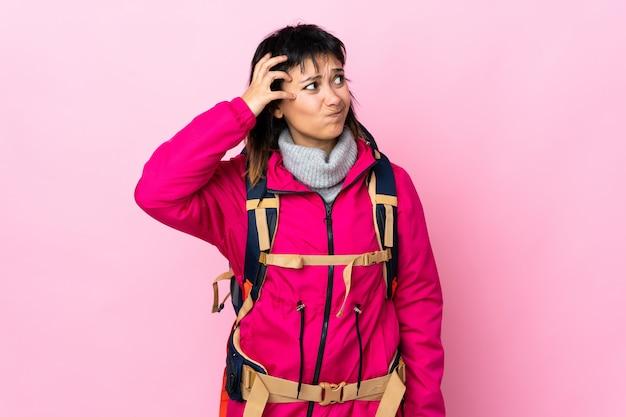 Ragazza giovane alpinista con un grande zaino sul rosa isolato con dubbi e con espressione faccia confusa