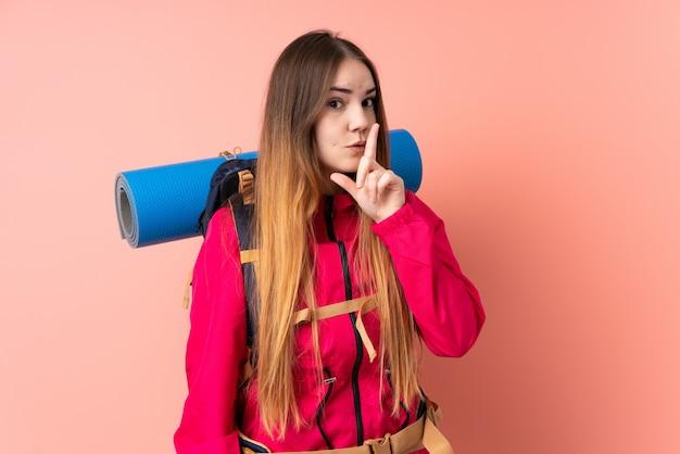 Ragazza giovane alpinista con un grande zaino sulla parete rosa che fa gesto di silenzio
