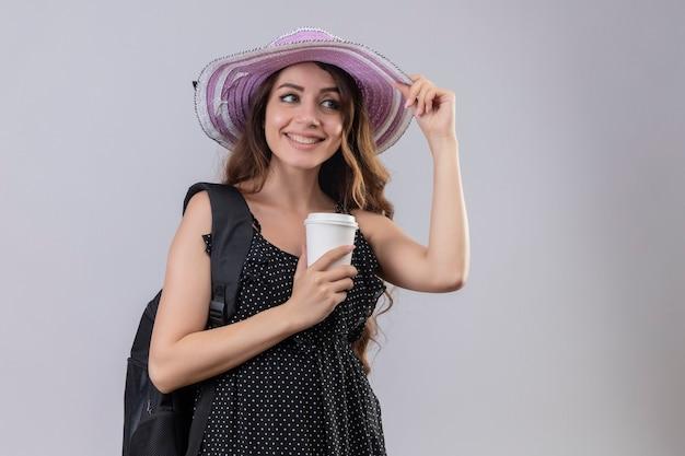 Ragazza giovane bella viaggiatore in cappello estivo con zaino tenendo la tazza di caffè sorridente allegramente felice e positivo in piedi su sfondo bianco