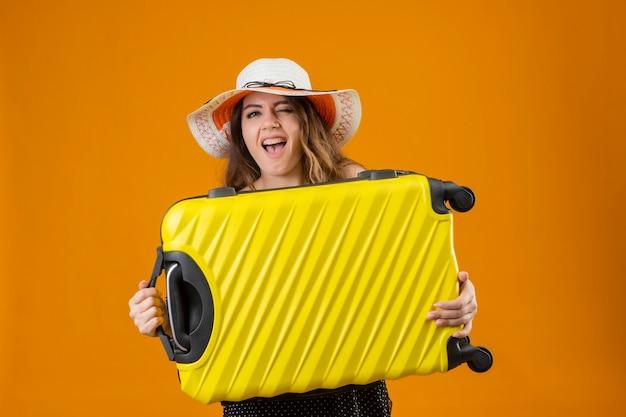 Ragazza giovane bella viaggiatore in vestito a pois in cappello estivo che tiene la valigia urlando felice pazzo in piedi su sfondo giallo