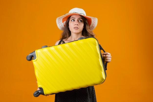 Ragazza giovane bella viaggiatore in vestito a pois in cappello estivo tenendo la valigia all'oscuro e confuso non avendo risposta su sfondo arancione