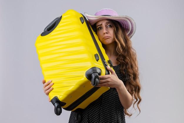 Ragazza giovane bella viaggiatore sconvolto in vestito a pois in cappello estivo che tiene la valigia che guarda l'obbiettivo con espressione triste sul viso in piedi sopra priorità bassa bianca