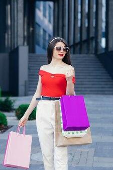 Ragazza giovane con borse della spesa colorate in giro per la città dopo lo shopping. consumismo, acquisti, shopping, concetto di stile di vita.