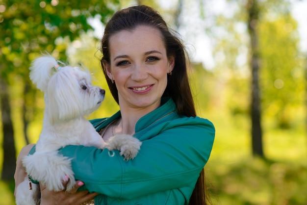 Ragazza giovane con il suo cane. il cucciolo di cane bianco corre con il suo proprietario. concezione sull'amicizia, l'animale e la libertà.
