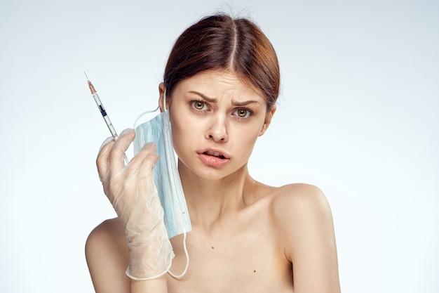 Ragazza giovane con una siringa per iniezione nella pelle