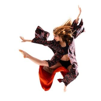 Ragazza giovane danza con kimono saltando