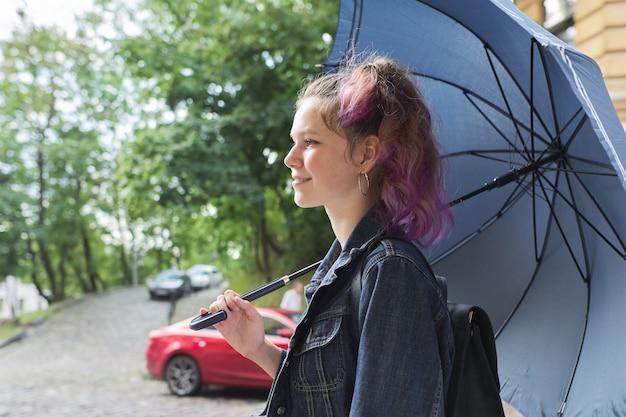 Ragazza giovane dell'adolescente sotto un ombrello sulla via di vecchia città