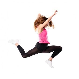 Ragazza giovane di ballo sopra il salto bianco isolato