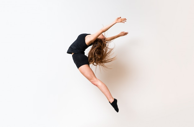 Ragazza giovane di ballo sopra la parete bianca isolata