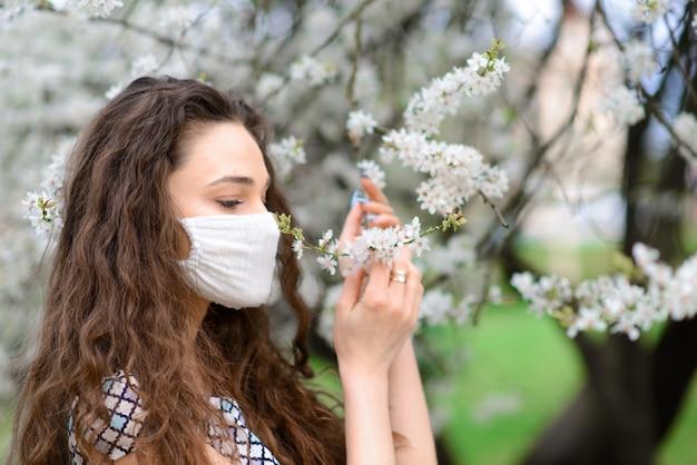 Ragazza, giovane donna in una mascherina medica sterile protettiva sul suo giardino del fronte in primavera. inquinamento atmosferico, virus, concetto di coronavirus pandemico.