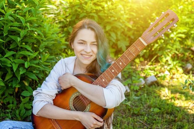 Ragazza giovane hipster seduto in erba e suonare la chitarra sul parco o giardino musica