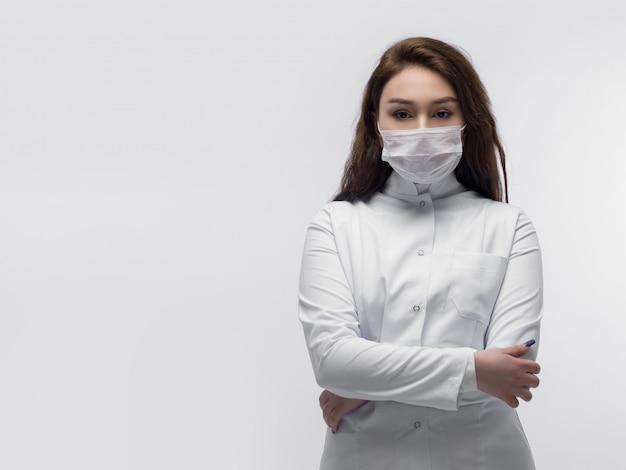 Ragazza giovane medico con maschera protettiva bianca con le mani incrociate