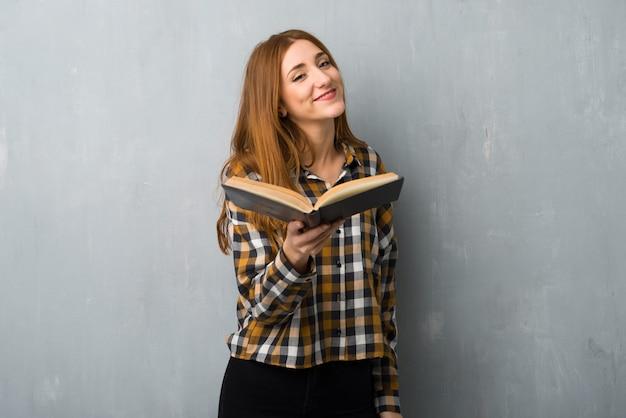 Ragazza giovane rossa sopra la parete del grunge in possesso di un libro e darlo a qualcuno