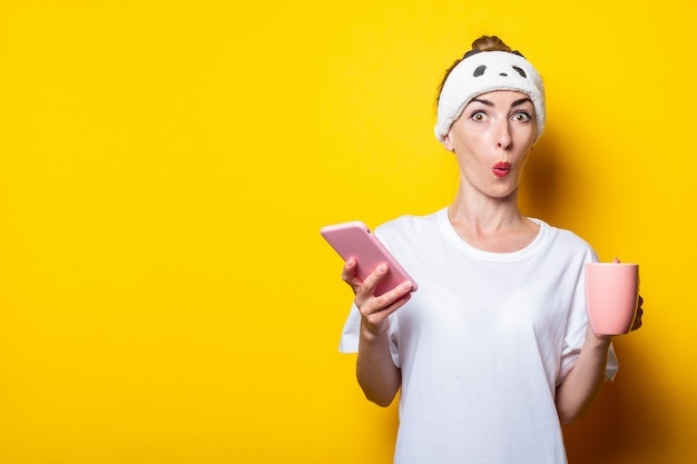Ragazza giovane sorpresa in una benda con un telefono e una tazza di caffè su uno sfondo giallo