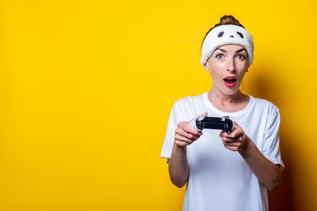 Ragazza giovane sorpresa in una maglietta bianca con un joystick in mano.