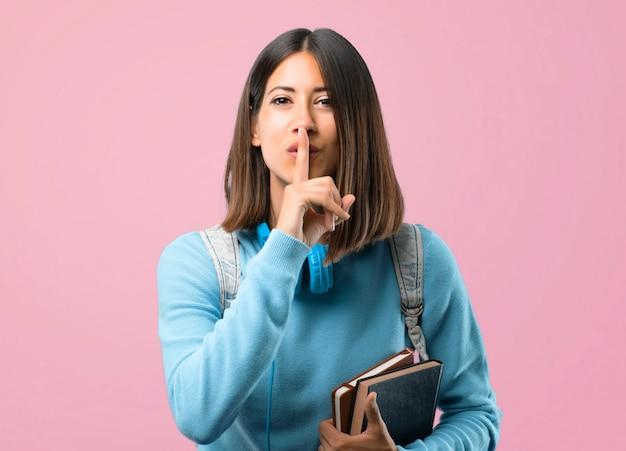 Ragazza giovane studente con maglione blu e cuffie mostrando un segno di chiusura della bocca.