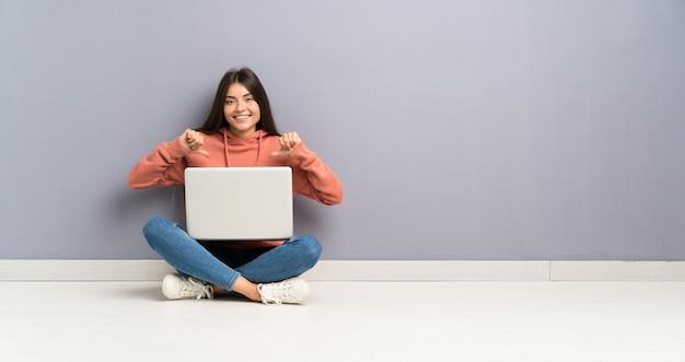 Ragazza giovane studente con un computer portatile sul pavimento orgoglioso e soddisfatto di sé