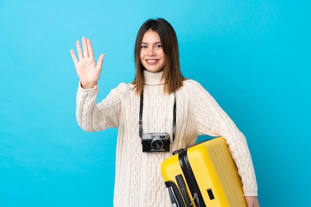 Ragazza giovane viaggiatore con la valigia sul muro blu