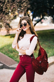 Ragazza glamour con i capelli lunghi in occhiali da sole è in posa sulla strada. ha il colore del marsala sui vestiti e sembra apprezzata.
