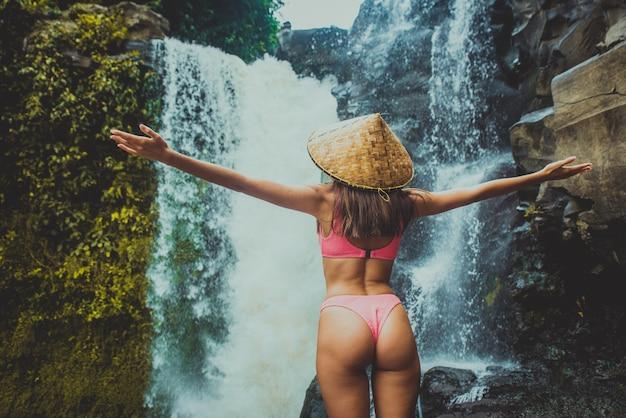 Ragazza graziosa alla cascata di tegenungan, bali