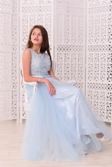 Ragazza graziosa alla moda che si siede sulla sedia a casa