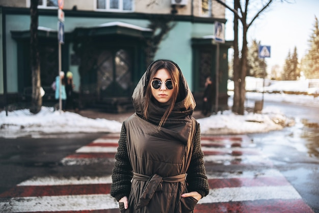 Ragazza graziosa che cammina sulla strada, orario invernale.